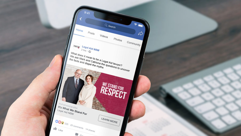 Hand holding a phone featuring a Facebook post for Legal Aid NSW's 'What Do You Stand For?' campaign